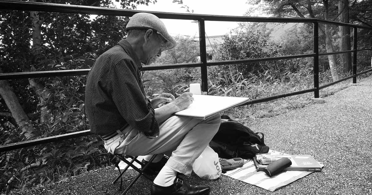 An elderly man sitting in a small seat drawing in a notebook.
