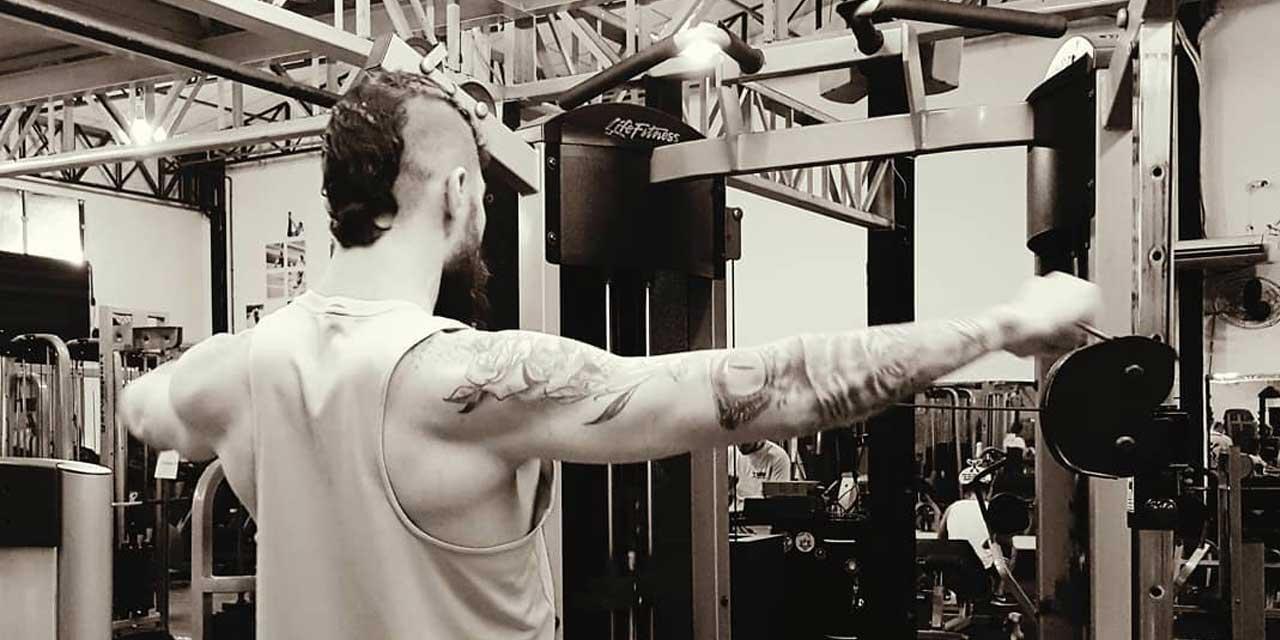 Imagem de uma pessoa de costas fazendo exercício na academia.