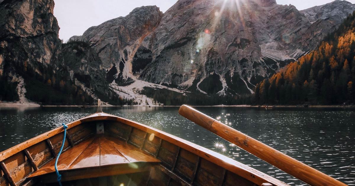 Vista de dentro de um barco de madeira em alto mar para uma montanha.