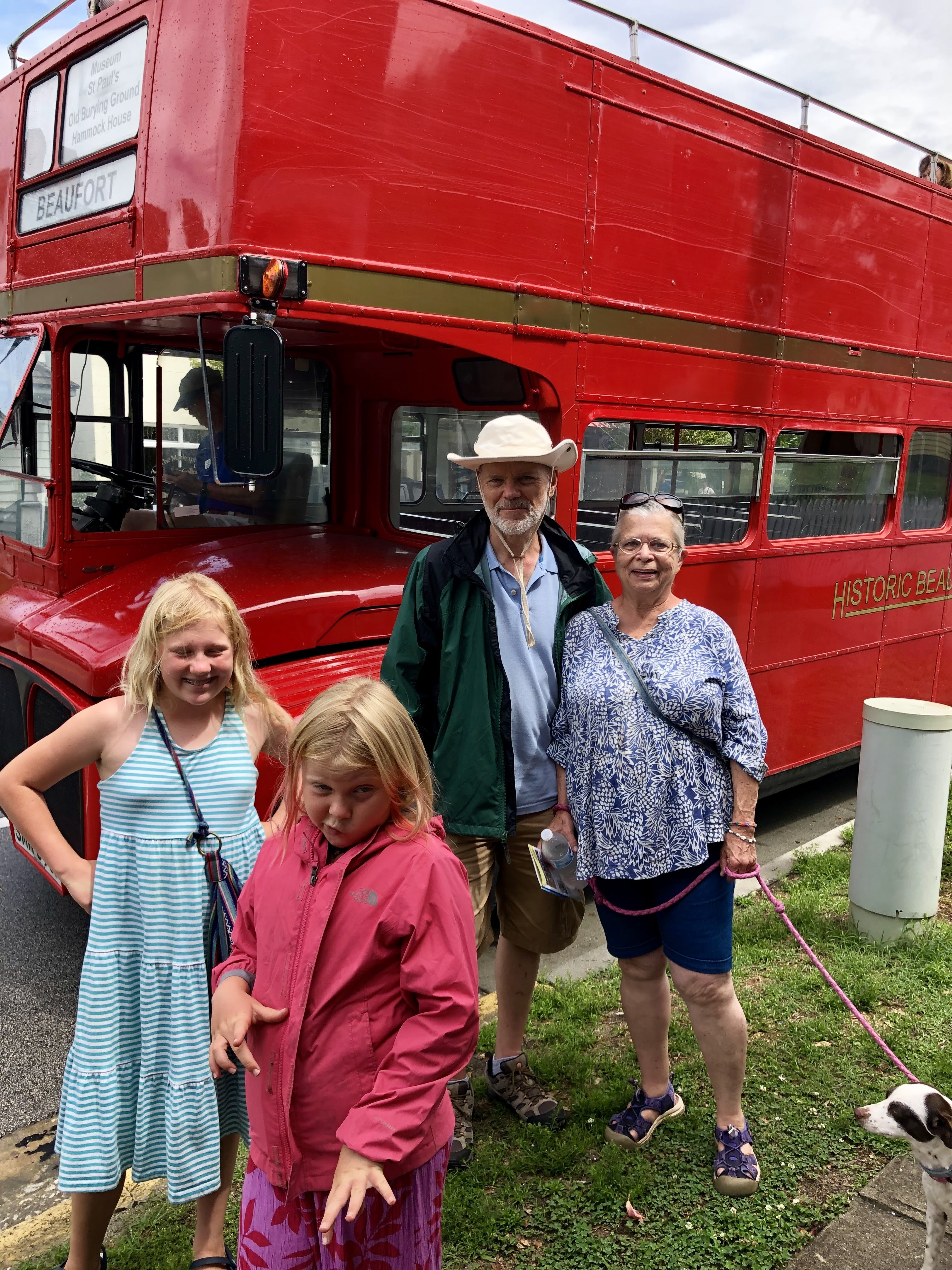 group in front of the double decker bus