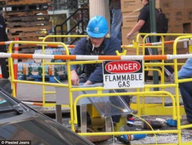 Man smoking a cigarette near a sign that says Danger - Flammable Gas