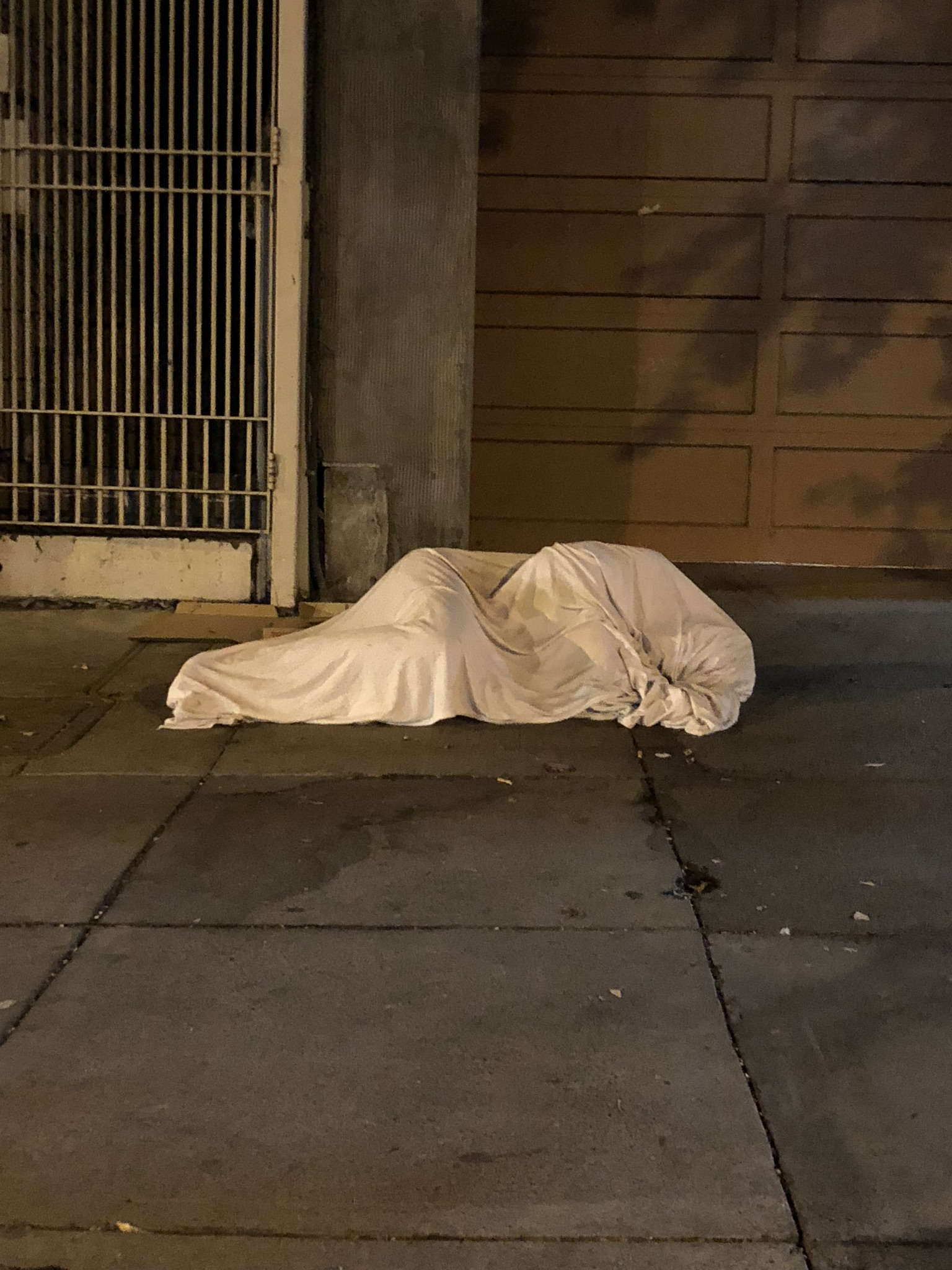 homeless person sleeping in fetal position on cold sidewalk fully wrapped in white sheet