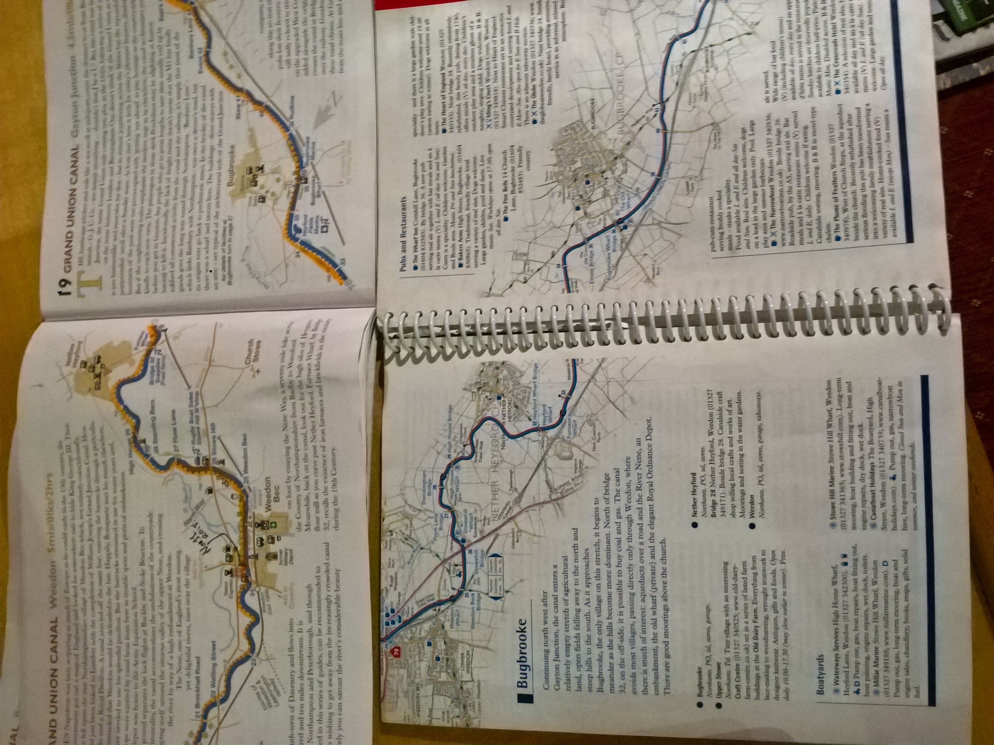 Photo of two open guidebooks with maps of the Grand Union Canal in Northamptonshire. The maps only include half a mile or a mile on either side of the canal, so they are very long and stretched out, cutting across the pages. The descriptive text wraps around the shape of the map.